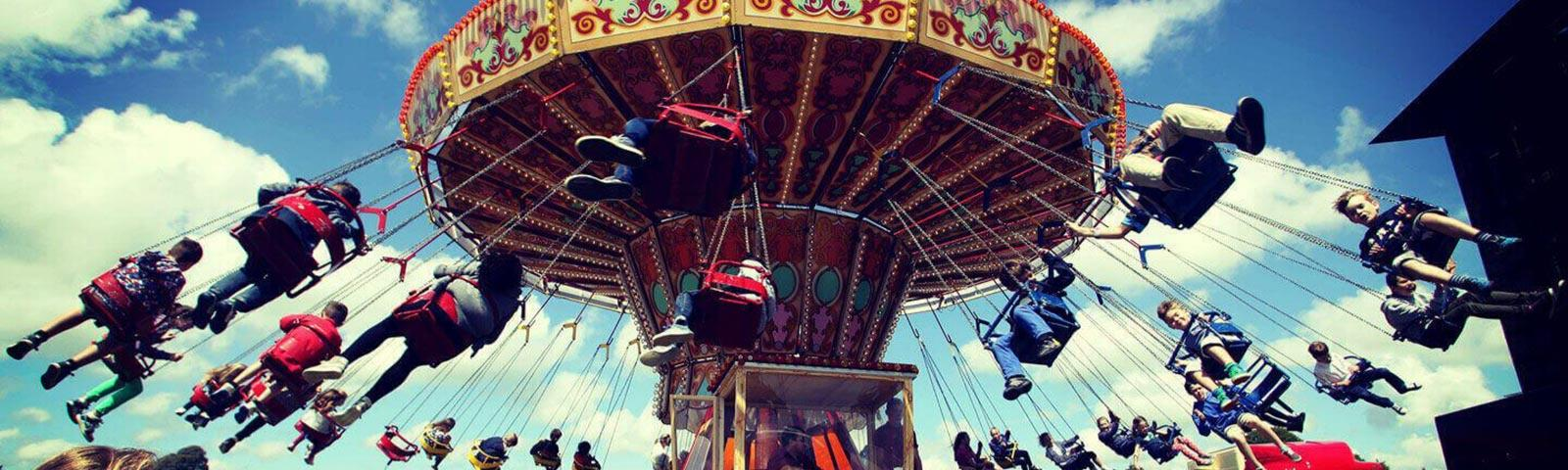 Kids sitting on a fun fair ride at an family event at Fontwell Park Racecourse.