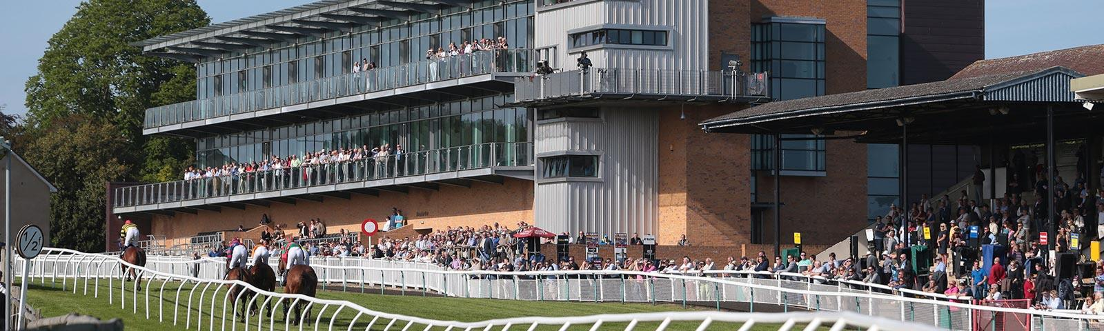 Crowds watching racing at Fontwell Park Racecourse, with the main grandstand building in the background.