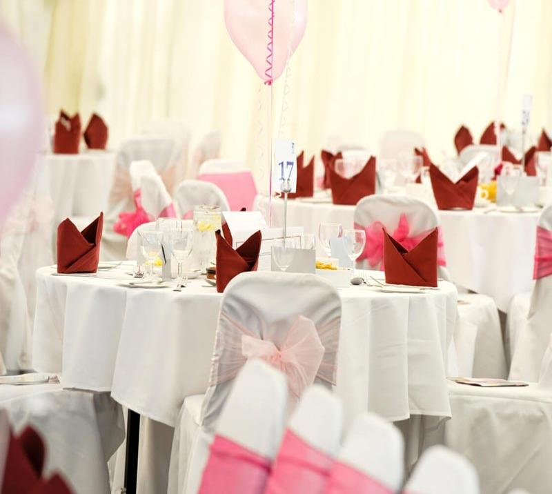 Cleanly prepared tables in white, pink and dark red.