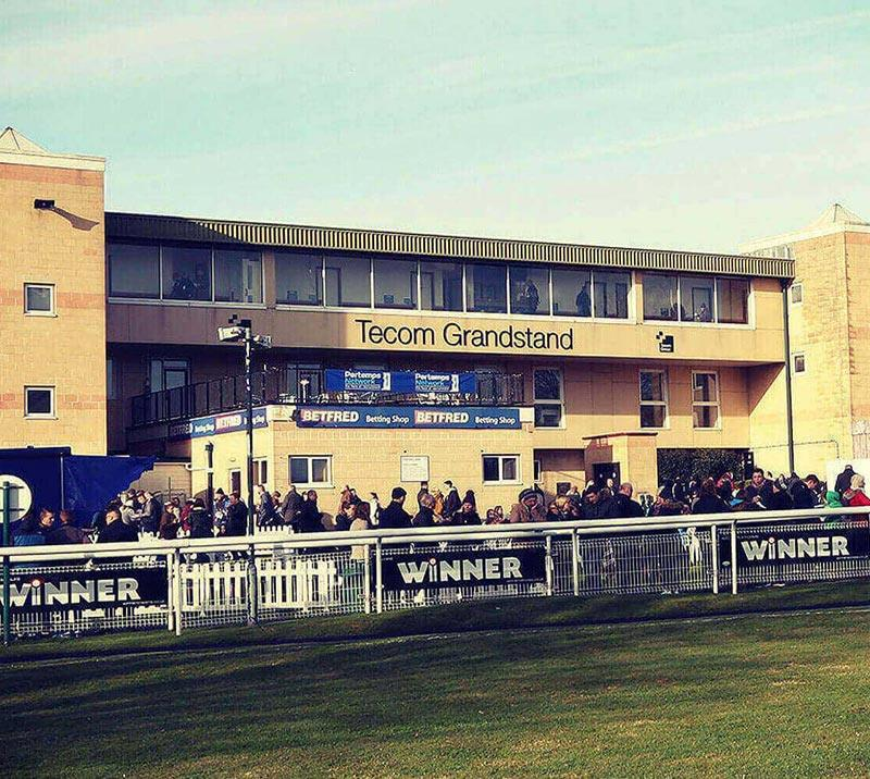 Crowds standing in front of the Tecom Grandstand at Fontwell Park Racecourse.