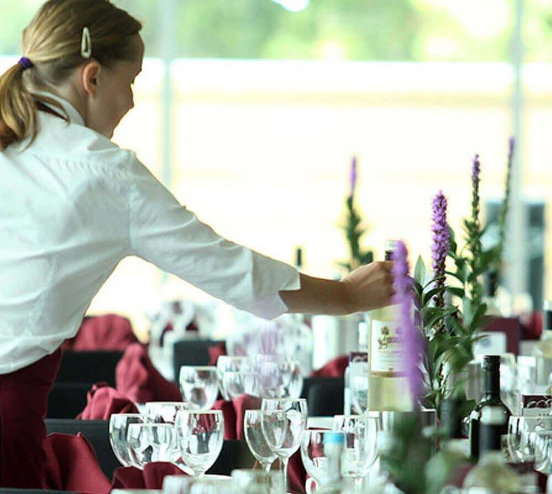 Waitress setting up a table in a restaurant.