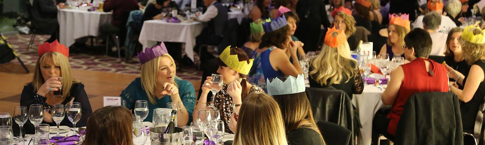 A crowd of Christmas revellers exchange humorous stories around dining tables.