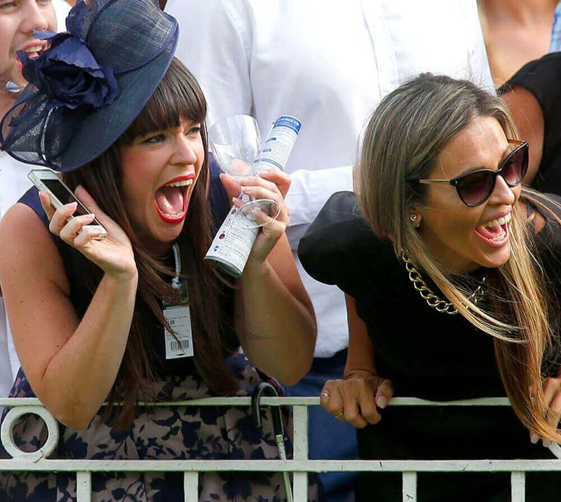 Two ladies cheering on while at the races  at Fontwell Park Racecourse.